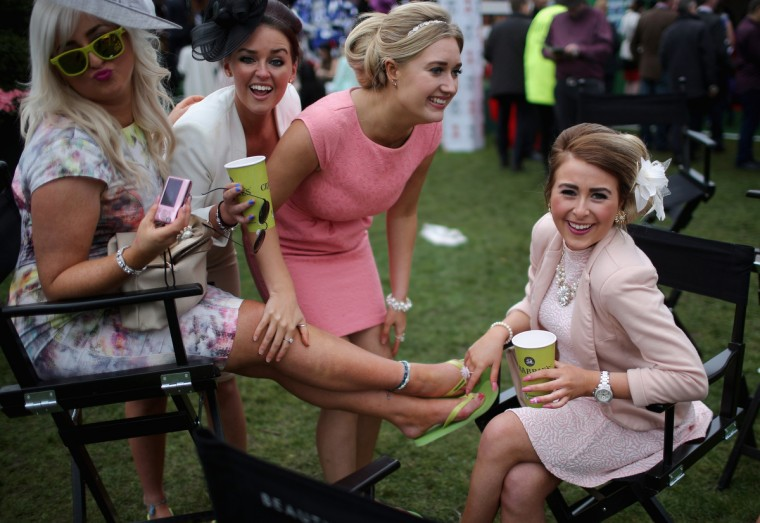 Racegoers enjoy the party atmosphere of Ladies Day and dress to impress at the Aintree Grand National Festival meeting on April 4, 2014 in Aintree, England. Friday is traditionally Ladies day at the three-day meeting of the world famous Grand National Festival where fashion and dressing to impress is as important as the racing. (Christopher Furlong/Getty Images)