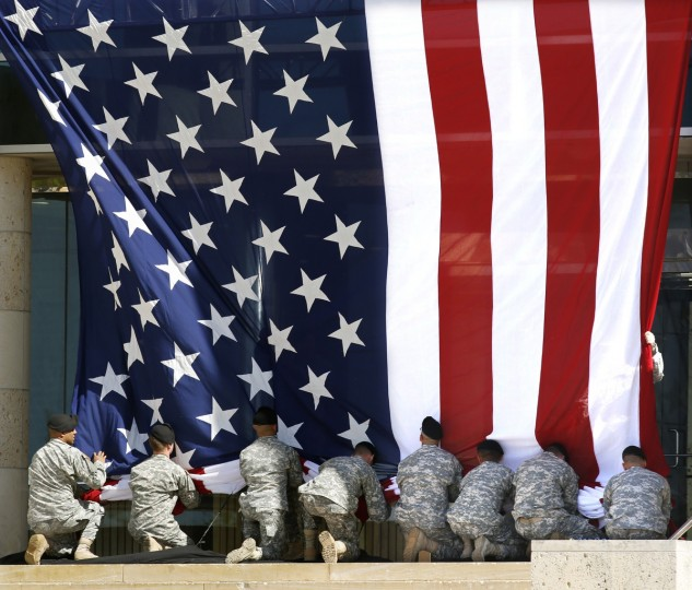 U.S. Army soldiers adjust an American flag before U.S. President Barack Obama speaks at a memorial for victims of last week's shooting on the U.S. Army post at Fort Hood military base in Kileen, Texas. During the shooting rampage on April 2, Army Spc. Ivan Lopez killed three people and wounded 16 others before taking his own life. (Erich Schlegel/Getty Images)