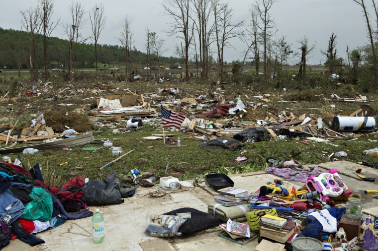 A flag that was found in debris was placed by volunteers working to help clean up after a strong tornado went through the area on April 27 for the second time in three years on April 28, 2014 in Vilonia, Arkansas. After deadly tornadoes ripped through the area and have left over a dozen dead, Mississippi, Arkansas, Texas, Louisiana, and Tennessee are all under watch as multiple storms over the next few days are expected. (Wesley Hitt/Getty Images)