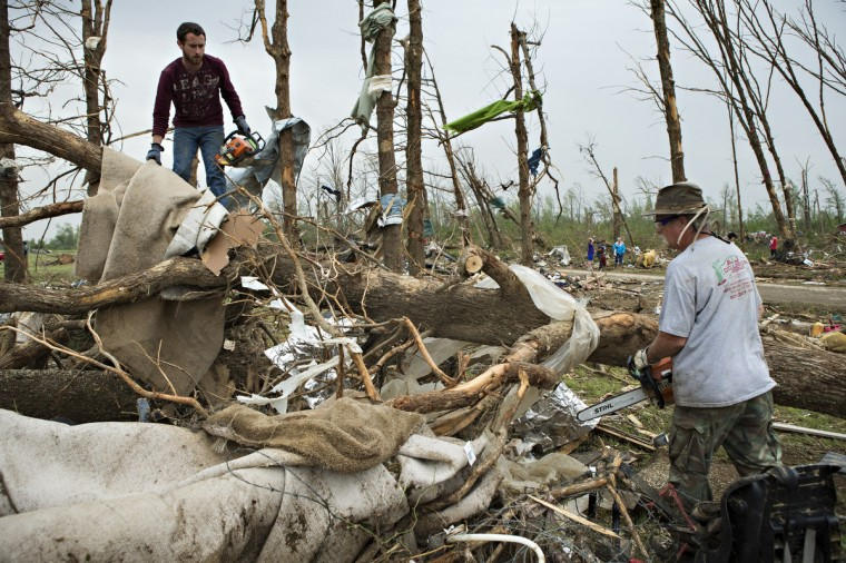 Eric Baker and Ron Smith use chainsaws and cut up trees after a strong tornado went through the area on April 27 for the second time in three years on April 28, 2014 in Vilonia, Arkansas. After deadly tornadoes ripped through the area and have left over a dozen dead, Mississippi, Arkansas, Texas, Louisiana, and Tennessee are all under watch as multiple storms over the next few days are expected. (Wesley Hitt/Getty Images)
