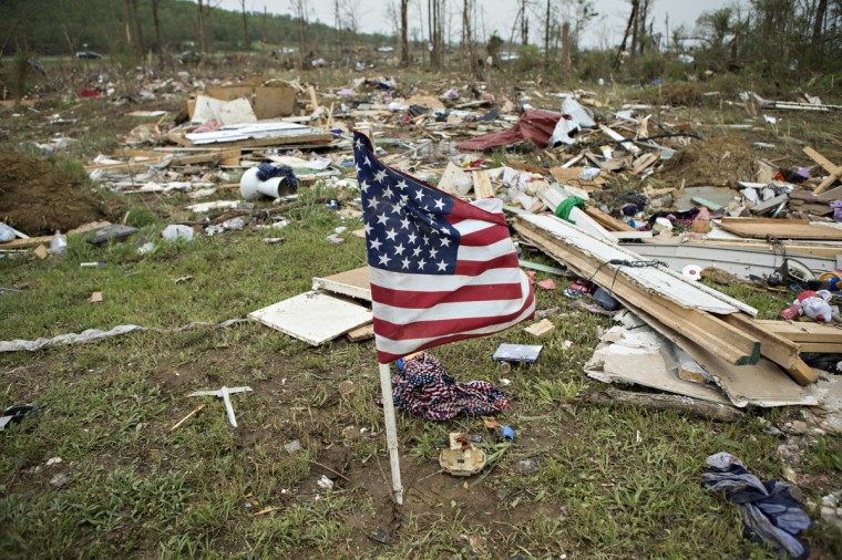 Flag that was found in debris was placed by volunteers working to help clean up after a strong tornado went through the area on April 27 for the second time in three years on April 28, 2014 in Vilonia, Arkansas. After deadly tornadoes ripped through the area and have left over a dozen dead, Mississippi, Arkansas, Texas, Louisiana, and Tennessee are all under watch as multiple storms over the next few days are expected. (Wesley Hitt/Getty Images)