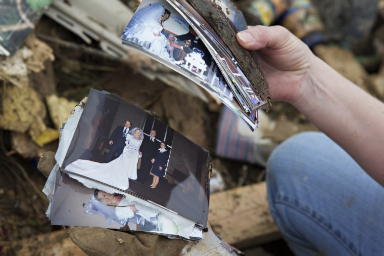 Lisa Taney, a volunteer, goes through wedding photos found in the mud near a destroyed trailer after a strong tornado went through the area on April 27 for the second time in three years on April 28, 2014 in Vilonia, Arkansas. After deadly tornadoes ripped through the area and have left over a dozen dead, Mississippi, Arkansas, Texas, Louisiana, and Tennessee are all under watch as multiple storms over the next few days are expected. (Wesley Hitt/Getty Images)