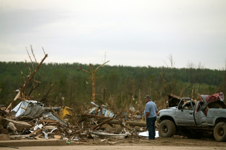 A passerby stops to look at damage caused by a tornado on Sunday evening, on April 29, 2014 in Vilonia, Arkansas. After deadly tornadoes ripped through the region leaving more than a dozen dead, Mississippi, Arkansas, Texas, Louisiana and Tennessee are all under watch as multiple storms are expected over the next few days. (Mark Wilson/Getty Images)
