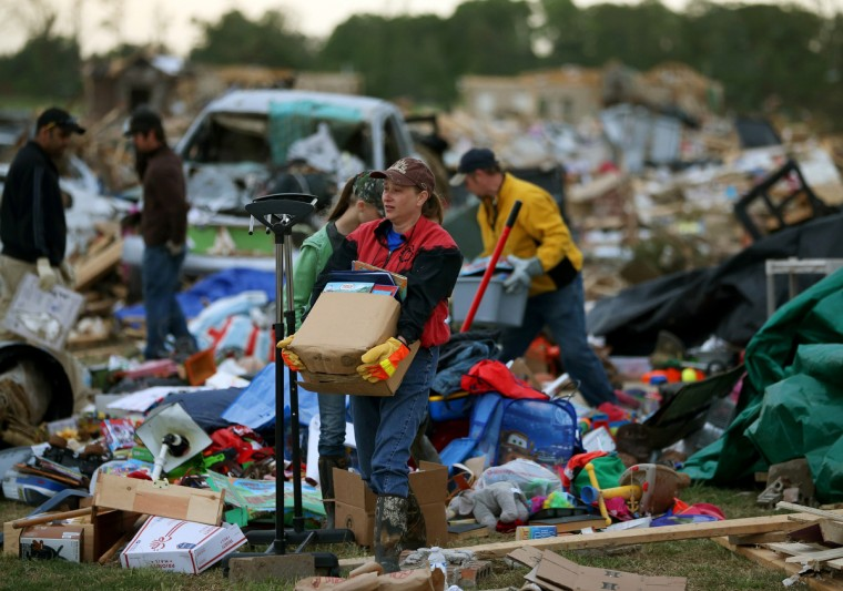 Volunteer Gina Lowe (C) helps a family move belongings from a home that was destroyed by a tornado on Sunday, April 29, 2014 in Vilonia, Arkansas. After deadly tornadoes ripped through the region leaving more than a dozen dead, Mississippi, Arkansas, Texas, Louisiana and Tennessee are all under watch as multiple storms are expected over the next few days. (Mark Wilson/Getty Images)