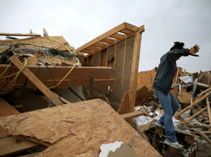 Michelle McGee walks over debris to inspect her home that was destroyed by a tornado on Sunday, April 29, 2014 in Vilonia, Arkansas. After deadly tornadoes ripped through the region leaving more than a dozen dead, Mississippi, Arkansas, Texas, Louisiana and Tennessee are all under watch as multiple storms over the next few days are expected. (Mark Wilson/Getty Images)