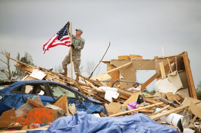 Arkansas National Guard Staff Sgt. Skipper Smith hangs an American flag on a pole at the site of a home that was detroyed when a tornado hit the area April 29, 2014 in Vilonia, Arkansas. Deadly tornadoes ripped through the region April 27, leaving more than a dozen dead. (Mark Wilson/Getty Images)