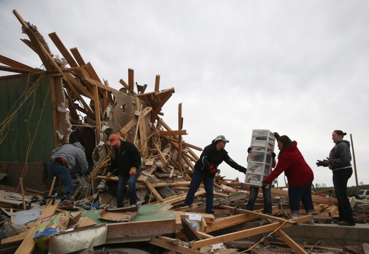 Volunteers help clean debris at the site of a home that was detroyed when a tornado hit the area, April 29, 2014 in Vilonia, Arkansas. Deadly tornadoes ripped through the region April 27, leaving more than a dozen dead. (Mark Wilson/Getty Images)
