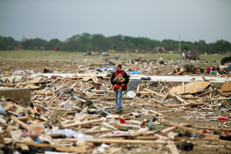 Resident Mark Wade looks through debris after the area was hit by a tornado April 29, 2014 in Vilonia, Arkansas. Deadly tornadoes ripped through the region April 27, leaving more than a dozen dead. (Mark Wilson/Getty Images)