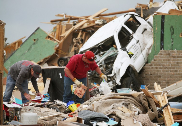 Gary Moore (R) looks through debris where his home once stood before it was destroyed by a tornado April 29, 2014 in Vilonia, Arkansas. Deadly tornadoes ripped through the region April 27, leaving more than a dozen dead. (Mark Wilson/Getty Images)
