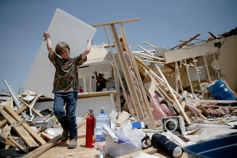 Sam Smith helps a family friend salvage what he can from his business that was destroyed by a tornado on April 29, 2014 in Tupelo, Mississippi. A deadly tornado ripped through the area April 28, after deadly storms moved through the south spawning tornadoes that have left more than a dozen dead. (Joe Raedle/Getty Images)