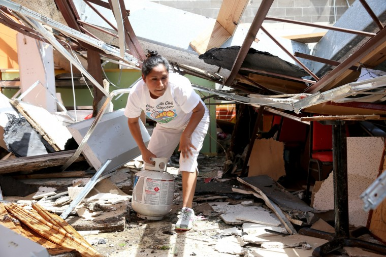 Isabel Jimenez salvages what she can from her restaurant after the building was destroyed by a tornado on April 29, 2014 in Tupelo, Mississippi. A deadly tornado ripped through the area April 28, after deadly storms moved through the south spawning tornadoes that have left more than a dozen dead. (Joe Raedle/Getty Images)