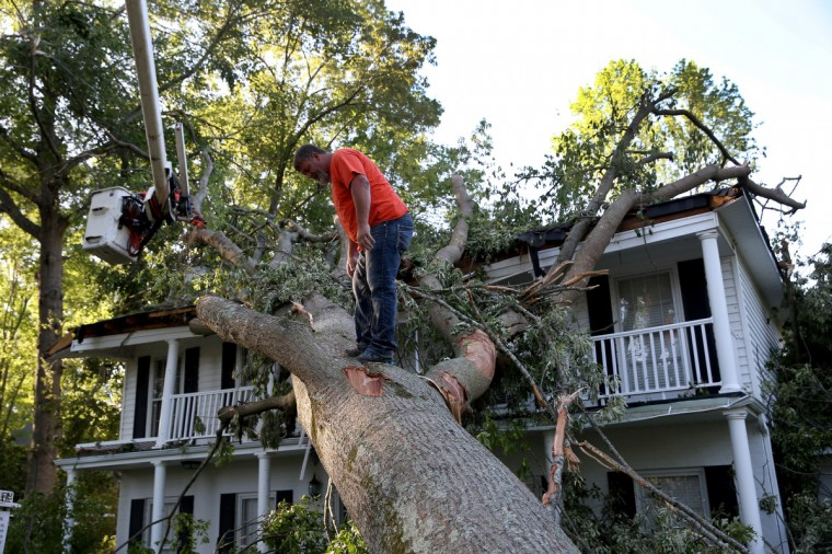 Rodney Stanford from Brewer Tree Service works on removing a tree that is resting on a home after a tornado struck on Monday, on April 30, 2014 in Tupelo, Mississippi. Deadly tornadoes ripped through the region over the last few days, leaving more than a dozen dead. (Joe Raedle/Getty Images)