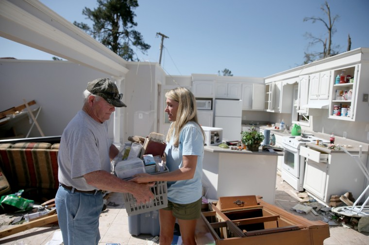 Jerry Estes (L) and his daughter, Cherie Bell, salvage items from his home that was damaged on Monday by a tornado on April 30, 2014 in Louisville, Mississippi. Deadly tornadoes ripped through the region starting on April 27 leaving more than two dozen dead. The storm system has also brought severe flooding to Florida's Panhandle. (Joe Raedle/Getty Images)