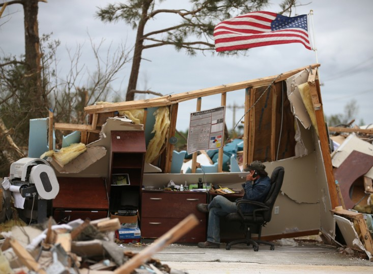 A man who wished not to be identified talks on a phone in a business that was destroyed by a tornado, April 30, 2014 in Mayflower, Arkansas. Deadly tornadoes ripped through the region starting on April 27 leaving more than two dozen dead. The storm system has also brought severe flooding to Florida's Panhandle. (Mark Wilson/Getty Images)