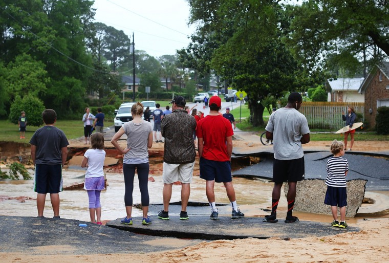 People survey the damage on Piedmont Street in the Cordova Park neighborhood after it washed out due to heavy rains on April 30, 2014 in Pensacola, Florida. A major storm system that brought tornadoes to regions of the South dumped more than two feet of water in a little over a day in the Florida Panhandle. (Marianna Massey/Getty Images)