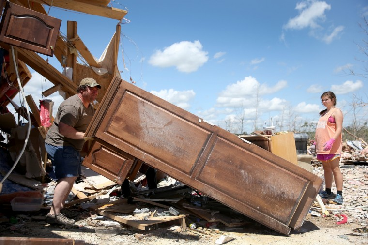 Paul Jackson lifts part of a wall unit that was in the kitchen as Marion Ming looks on while they salvage what they can in a relative's home after it was destroyed on Monday by a tornado on April 30, 2014 in Louisville, Mississippi. Deadly tornadoes ripped through the region starting on April 27 leaving more than two dozen dead. The storm system has also brought severe flooding to Florida's Panhandle. (Joe Raedle/Getty Images)