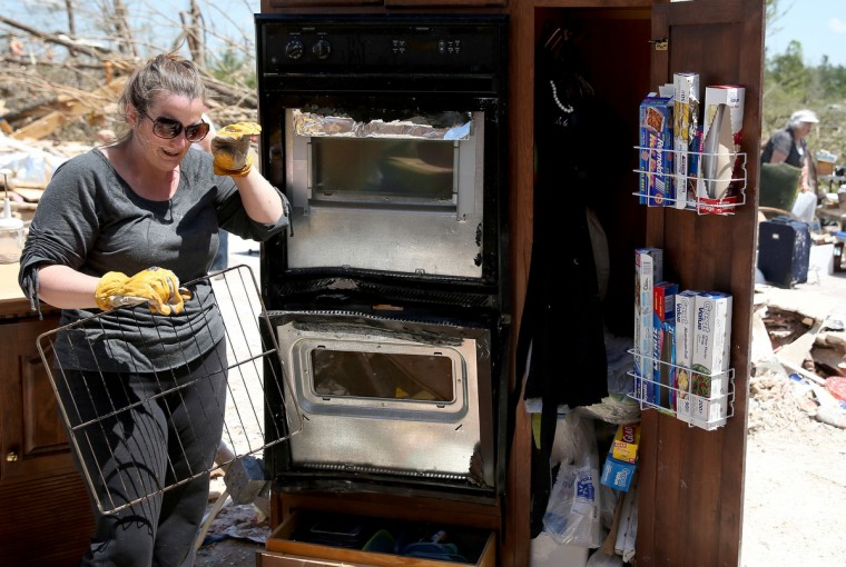 Marla Jackson salvages what she can from the area that was the kitchen in her parents home after it was destroyed on Monday by a tornado on April 30, 2014 in Louisville, Mississippi. Deadly tornadoes ripped through the region starting on April 27 leaving more than two dozen dead. The storm system has also brought severe flooding to Florida's Panhandle. (Joe Raedle/Getty Images)