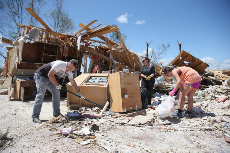 Ryan Smyth, Marla Jackson and Marion Ming (L-R) salvage what they can from the area that was the kitchen in a relative's home after it was destroyed on Monday by a tornado on April 30, 2014 in Louisville, Mississippi. Deadly tornadoes ripped through the region starting on April 27 leaving more than two dozen dead. The storm system has also brought severe flooding to Florida's Panhandle. (Joe Raedle/Getty Images)