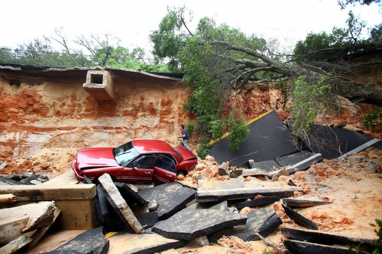 People survey the damage on Scenic Highway after part of the highway collapsed following heavy rains and flash flooding on April 30, 2014 in Pensacola, Florida. A major storm system that brought tornadoes to regions of the South dumped more than two feet of water in a little over a day in the Florida Panhandle. (Marianna Massey/Getty Images)