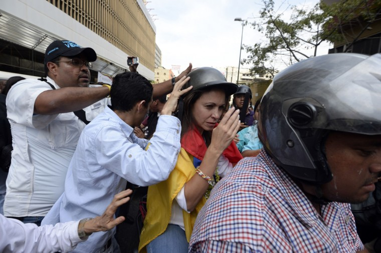 Supporters of Venezuelan opposition lawmaker Maria Corina Machado (C) put a helmet on her head as she leaves an administrative office dependent on the National Assembly, in Caracas. In a direct challenge to President Nicolas Maduro, prominent opposition politician Machado vowed to take her seat in the National Assembly despite her ouster by the Supreme Court. The head of the legislative body had ordered Machado expelled and her parliamentary immunity stripped last week after she tried to speak before the Organization of American States about her country's crisis. (Juan Barreto/Getty Images)
