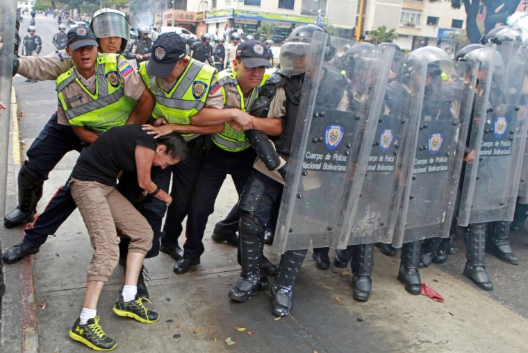 An anti-government activist clashes with riot police during a protest in Caracas. In a direct challenge to President Nicolas Maduro, prominent opposition politician Maria Corina Machado vowed to take her seat in the National Assembly despite her ouster by the Supreme Court. The head of the legislative body had ordered Machado expelled and her parliamentary immunity stripped last week after she tried to speak before the Organization of American States about her country's crisis. (Federico Parra/Getty Images)