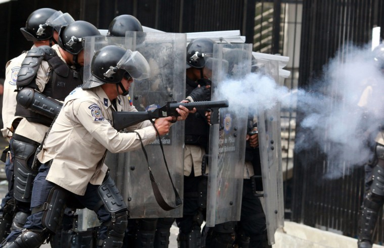 Riot policemen take positions during an anti-government protest in Caracas. In a direct challenge to President Nicolas Maduro, prominent opposition politician Maria Corina Machado vowed to take her seat in the National Assembly despite her ouster by the Supreme Court. The head of the legislative body had ordered Machado expelled and her parliamentary immunity stripped last week after she tried to speak before the Organization of American States about her country's crisis. (Federico Parra/Getty Images)