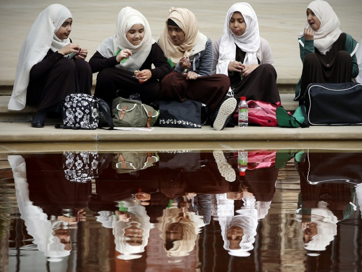 Young girls eat their lunch beside a pond at the V&A Museum in London. (Adrian Dennis/Getty Images)