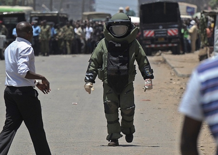 """A Kenyan police bomb expert clad in a protective ballistic suit approaches the site of a suspected improvised explosive device, IED, in Nairobi's increasingly restive Somali district of Eastleigh, a day after a prominent hardline Muslim cleric was shot dead in Mombasa. The cleric Abubaker Shariff Ahmed, was a vocal supporter of Osama bin Laden, and was on UN sanctions lists accused of being a """"leading facilitator and recruiter of young Kenyan Muslims for violent militant activity in Somalia"""", and of having """"strong ties"""" with Shebab leaders. (Tony Karumba/Getty Images)"""