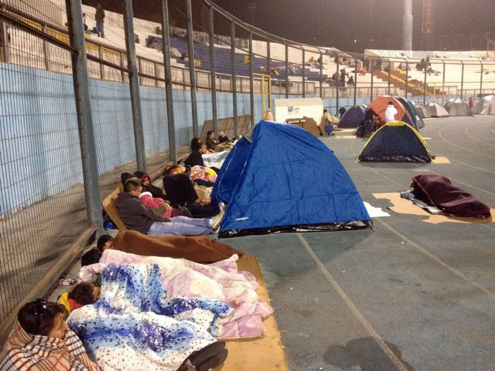 Locals take refuge at the city stadium following a tsunami alert after a powerful 8.0-magnitude earthquake hit off Chile's Pacific coast, on April 2, 2014 in Iquique. A tsunami warning has been issued for Chile, Peru and Ecuador, US officials said. The quake struck at a depth of 10 kilometers (six miles), 83 kilometers from Iquique on Chile's northern coast, the United States Geological Survey (USGS) said. (Aldo Solimano/Getty Images)