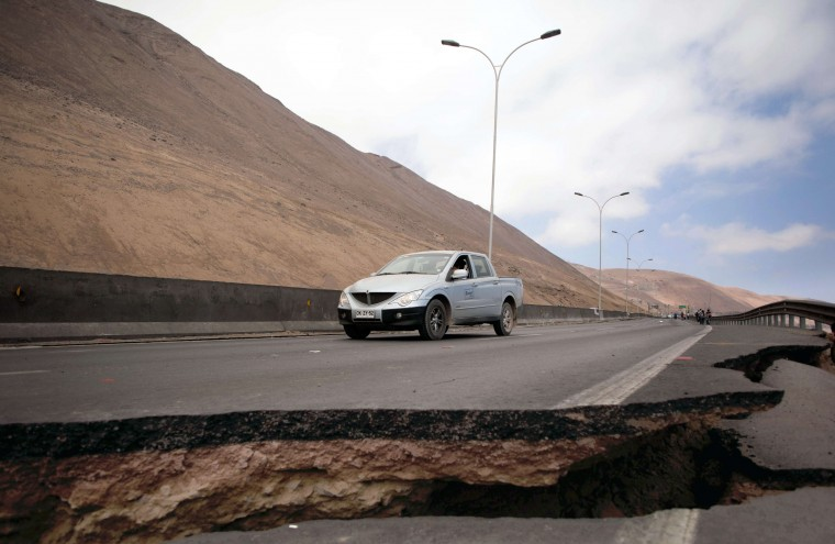 A car stops by a crack on a road damaged by a powerful 8.2-magnitude earthquake that hit off Chile's Pacific coast, in Iquique, northern Chile, on April 2, 2014. An 8.2-magnitude earthquake hit Chile late Tuesday, killing at least six people and generating tsunami waves that might ripple as far as Indonesia. (Juan Leonel/AFP/Getty Images)