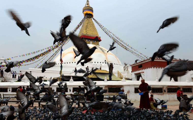A Budddhist monk (R) feeds pigeons at the Boudhanath Stupa in Kathmandu on April 3, 2014. The Stupa, which is situated on the outskirts of Kathmandu, is at the heart of the Nepalese capital's Tibetan community and is an important centre of Buddhist studies. (Prakash Mathema/AFP/Getty Images)