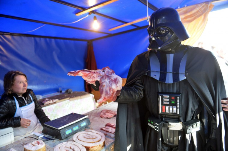 A man wearing the outfit of iconic movie villain Darth Vader grabs a piece of meat from a market stall within a protest action in front of the Central Election Commission building in Kiev. (Sergei Supinsky/Getty Images)