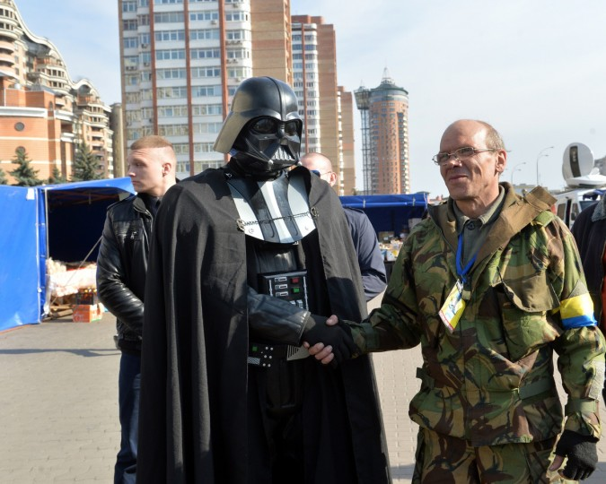 A man dressed as Darth Vader (L) shakes hand with a Maidan self-defense activist in front of the Central Election Commission building in Kiev. (Sergei Supinsky/Getty Images)