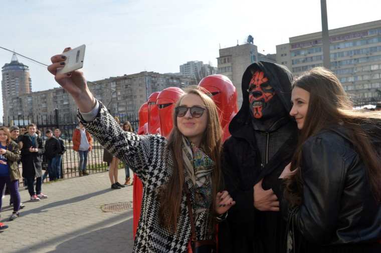 "Young women take a ""selfie"" with a man wearing the outfit of iconic movie villain Darth Maul (2nd R), surrounded by men dressed as Emperor's Royal Guards, during a protest action in front of the Central Election Commission building in Kiev. (Sergei Supinsky/Getty Images)"