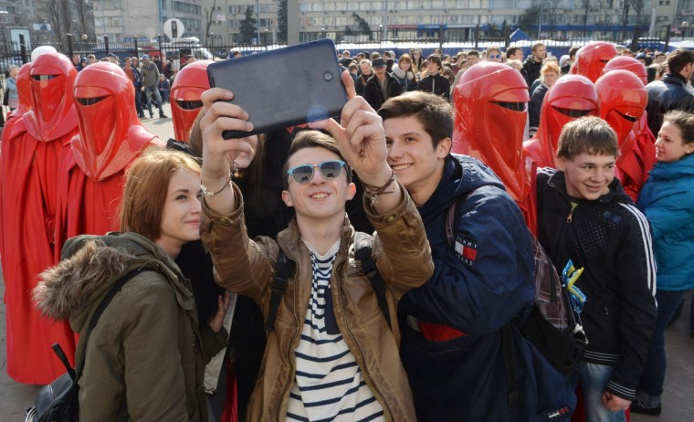 "Young men take a ""selfie"" with men dressed as the movie Star Wars Emperor's Royal Guards, during a protest action in front of the Central Election Commission building in Kiev. (Sergei Supinsky/Getty Images)"