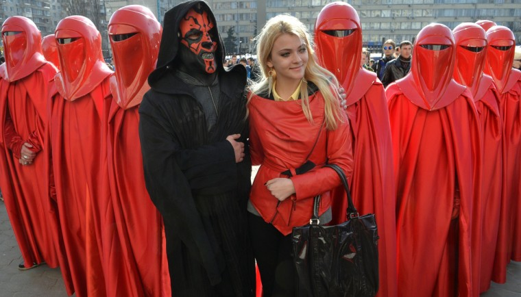 A young woman (C) poses with a man wearing the outfit of iconic movie villain Darth Maul (4th L), surrounded by men dressed as Emperor's Royal Guards, during a protest action in front of the Central Election Commission building in Kiev. (Sergei Supinsky/Getty Images)
