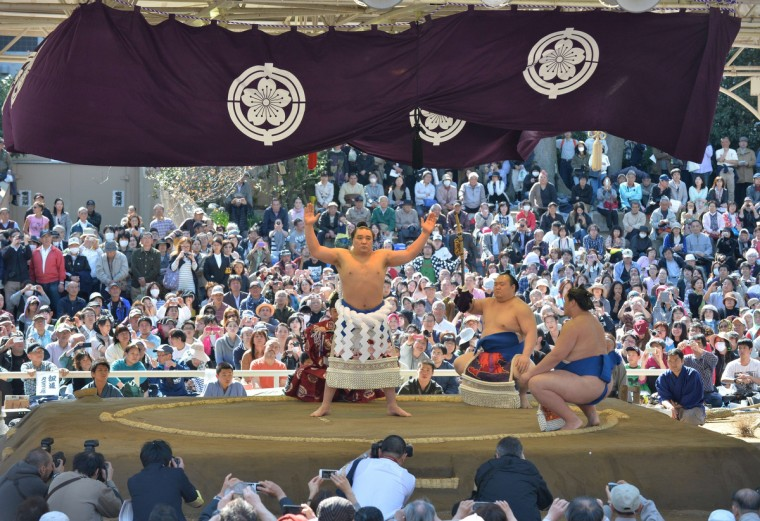 "Yokozuna or sumo grand champion Harumafuji of Mongolia (C) offers a ritual entrance into the sumo wrestling ring during a ""honozumo,"" a ceremonial sumo exhibition at Yasukuni shrine in Tokyo on April 4, 2014. (Kazuhiro Nogi/Getty images)"
