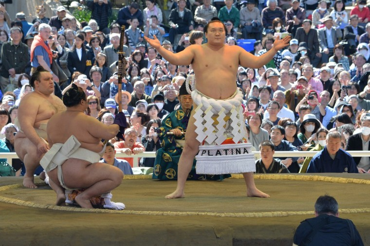 "Yokozuna Hakuho of Mongolia (C) offers a ritual entrance into the sumo wrestling ring during a ""honozumo,"" a ceremonial sumo exhibition at Yasukuni shrine in Tokyo on April 4, 2014. (Kazuhiro Nogi/Getty images)"