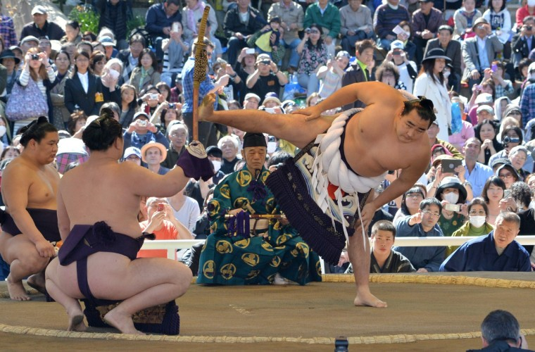 "Yokozuna Kakuryu of Mongolia (R) offers a ritual entrance into the sumo wrestling ring during a ""honozumo,"" a ceremonial sumo exhibition at Yasukuni shrine in Tokyo on April 4, 2014. (Kazuhiro Nogi/Getty images)"