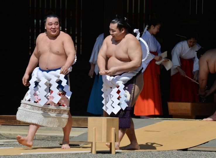 Mongolian-born both yokozuna Kakuryu (R) and Harumafuji (L) walk together as they attend a traditional Shinto ceremony at Yasukuni shrine in Tokyo on April 4, 2014. (Kazuhiro Nogi/Getty images)