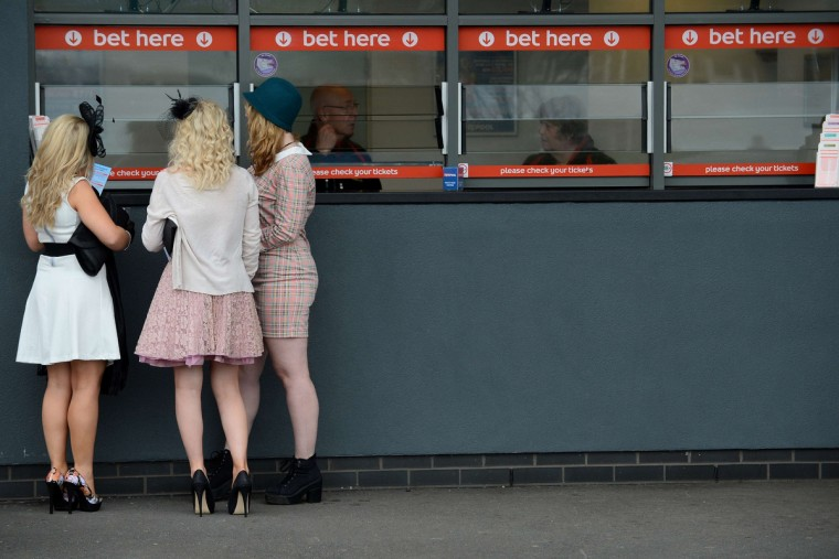 "Race goers preapre to place their bets during ""Ladies Day"" at the Grand National horse race meeting at Aintree in Liverpool, northwest England, on April 4, 2014. (Andrew Yates/Getty Images)"