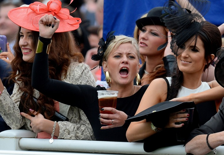 "Racegoers react during the first race of""Ladies Day"" at the Grand National horse race meeting at Aintree in Liverpool, northwest England, on April 4, 2014. (Andrew Yates/Getty Images)"