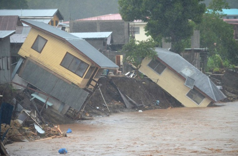 TOPSHOTS Flood waters run past damaged homes in the Solomon Islands' capital Honiara on April 4. Flash flooding killed at least three people and left 10,000 homeless in Honiara on April 4, with another 30 missing and the death toll expected to rise, aid workers said. || CREDIT: CARLOS ARUAFUCARLOS ARUAFU/ - AFP/GETTY IMAGES