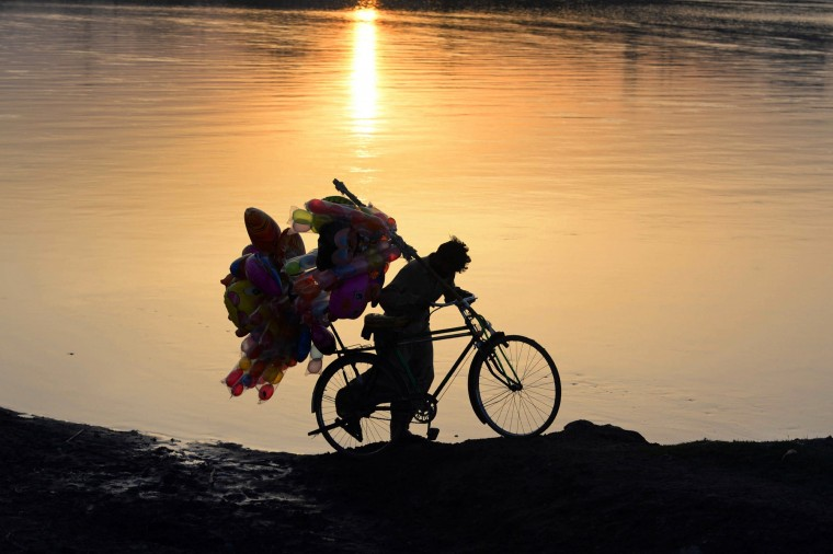 A Pakistani balloon vendor pushes his bicycle along the Ravi river during sunset in Lahore on April 4. Pakistan's economists had set a growth target for the current financial year of 4.4 percent, and the central bank in earlier reports had forecast growth of four percent. || CREDIT: ARIF ALI - AFP/GETTY IMAGES