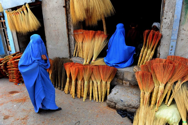 Afghan shoppers look for brooms at a roadside shop in Herat. Leading candidates in Afghanistan's presidential election voiced concern that voting was tainted by fraud after millions defied Taliban threats and turned out to choose a successor to President Hamid Karzai. World leaders praised the courage of Afghan voters, who cast their ballots in force despite bad weather and the violent campaign of intimidation, and urged patience in the long vote count. (Aref Karimi/Getty Images)