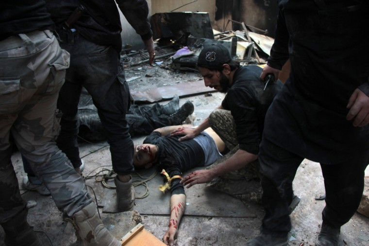 A wounded opposition fighter lies on the ground after he was injured during clashes with government forces in the northern Syrian city of Aleppo. Aleppo has been effectively divided into regime control in the west and rebel control in the east since shortly after fighting began there in the middle of 2012. (Medo Halab/Getty Images)
