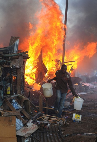 A Kenyan men with buckets of water works to put out a fire caused by an electrical fault from one of the residences, as it razes houses in Deep Sea slum in Nairobi. There is a high risk of fire in Nairobis slums and informal settlements due to the homes being poorly constructed and the materials used of inferior quality. In addition, people live in overcrowded conditions, and electrical connections, where they exist, are often unsafe. (Simon Maina/Getty Images)
