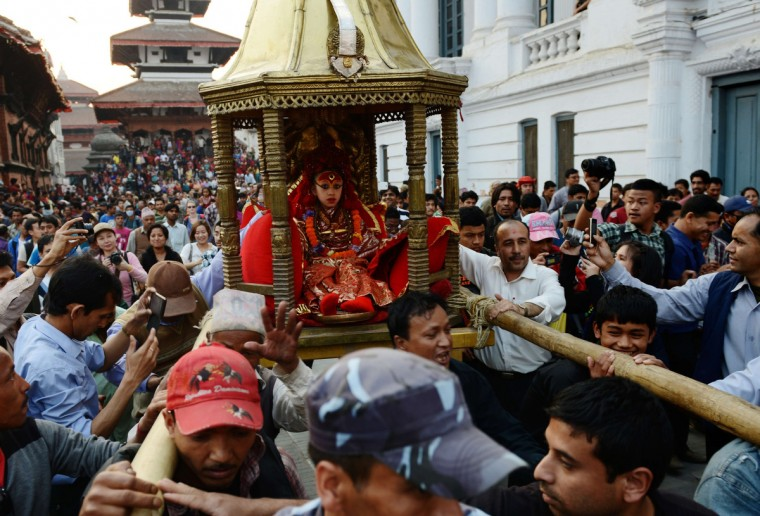 "Nepalese worshippers carry the Living Goddess ""Kumari Devi"" during a procession on the last day of the Seto (White) Machindranath chariot festival in Kathmandu. The Kumari is worshipped by both Hindus and Buddhists as a living goddess and protector bringing good luck and prosperity. Hindu and Buddhist devotees from the ethnic Newar community of Kathmandu valley celebrate the Seto Machindranath festival by pulling wooden chariots across the city. (Prakash Mathema/Getty Images)"