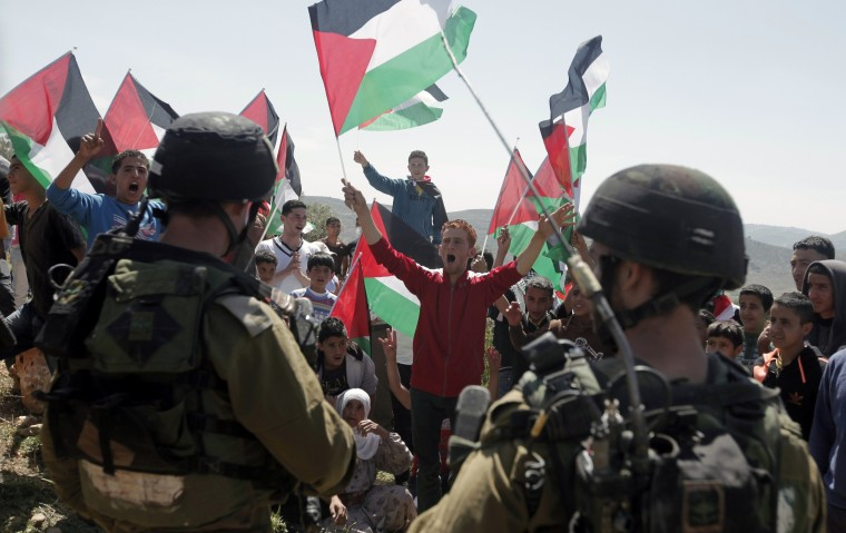 Palestinian protesters hold their national flag shouting slogans in front of Israeli security forces during a weekly protest against the confiscation of land by Israel on April 11, 2014 in the northern West Bank village of Salem, east of Nablus.  || CREDIT: JAAFAR ASHTIYEH - AFP/GETTY IMAGES