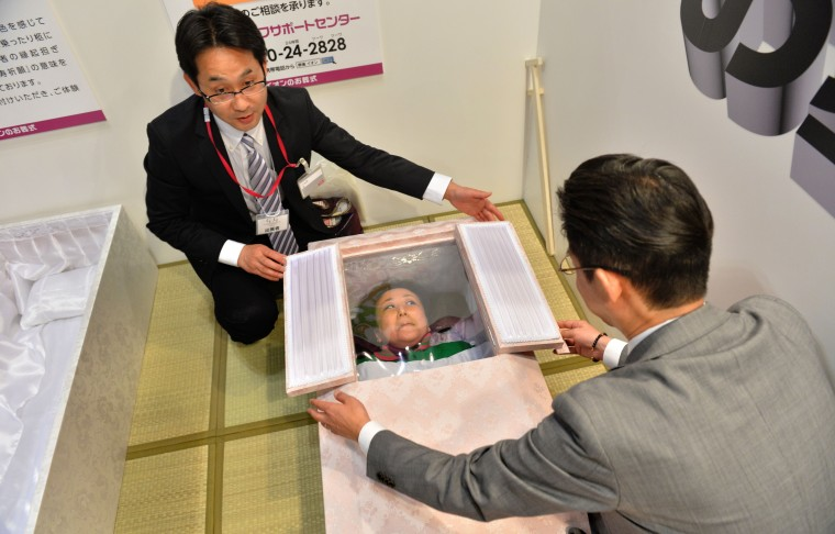 TOPSHOTS A woman lies in a coffin at a funeral fair in the Grand Generation's Collection 2014 produced by Japanese retailer Aeon in Makuhari on April 11, 2014.  The three-day collection will be held until April 13.        || CREDIT: KAZUHIRO NOGI - AFP/GETTY IMAGES